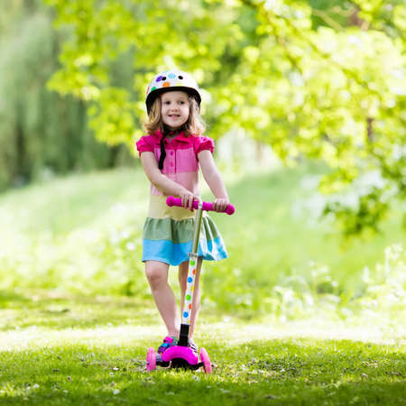 Piccolo bambino che impara a guidare uno scooter in un parco cittadino sulla soleggiata giornata estiva. Ragazza sveglia del bambino in età prescolare nel casco di sicurezza che guida un rullo. I bambini giocano all'aperto. Tempo libero attivo e sport all'aperto per bambini.