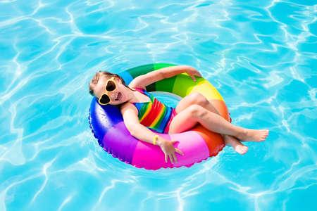 夏の暑い日に屋外スイミング プールでカラフルなインフレータブル リングと遊ぶ幸せな女の子。子供たちは泳げるようになります。子供の水のおも 写真素材
