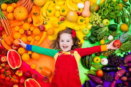 Meisje met verscheidenheid van groenten en fruit. Kleurrijke regenboog van rauwe verse groenten en fruit. Kind dat gezonde snack eet. Vegetarische voeding voor kinderen. Vitaminen voor kinderen. Uitzicht van boven.