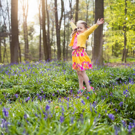 Child with bluebells. Little girl in pretty dress playing in beautiful spring forest with purple bluebell flowers. Kids hiking in park with blue bell flower meadow. Preschooler exploring nature.