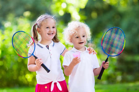 shuttlecock: Active preschool girl and boy playing badminton in outdoor court in summer. Kids play tennis. School sports for children. Racquet and shuttlecock sport for child athlete. Kid with racket and shuttle. Stock Photo