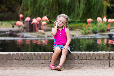 safari animal: Kids watch animals and birds at the zoo. Children watching wild life at safari park. Family day feeding animal at city zoo or farm. Little girl exploring nature and wildlife. Summer day trip. Stock Photo
