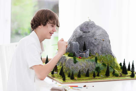 working on school project: Teenager working on model building school project. Kids build miniature scale model mountain for geography class in high school. Extracurricular activities and hobby club. Art and crafts for child.