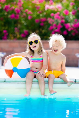 Kids playing at outdoor swimming pool. Little girl and boy play and swim in resort pool on tropical beach island summer family vacation. Swim and eye wear, sun protection, water toys for children.