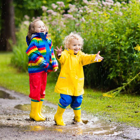 rain weather: Little boy and girl play in rainy summer park. Children with colorful rainbow jacket and waterproof boots jump in puddle and mud in the rain. Kids walk in autumn shower. Outdoor fun by any weather.