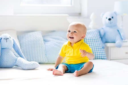 Baby playing on parents bed. Cute funny little boy learning to crawl in white sunny nursery. Infant and toddler room interior. Bedding and toys for kids. Children play at home. Baby bedroom. Stock Photo