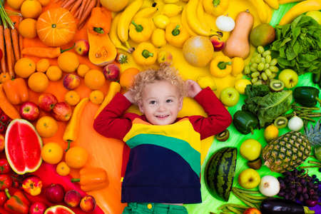 green bean: Baby boy with variety of fruit and vegetable. Colorful rainbow of raw fresh fruits and vegetables. Child eating healthy snack. Vegetarian nutrition for kids. Vitamins for children. View from above.