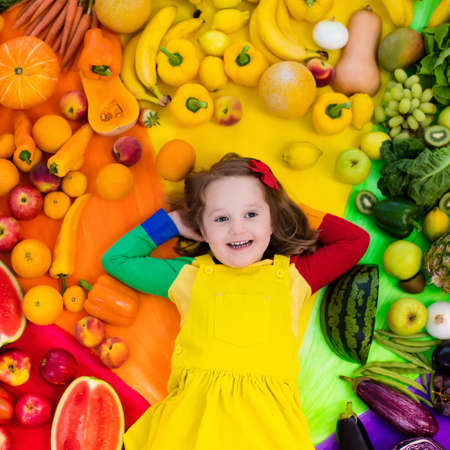 green bean: Little girl with variety of fruit and vegetable. Colorful rainbow of raw fresh fruits and vegetables. Child eating healthy snack. Vegetarian nutrition for kids. Vitamins for children. View from above.