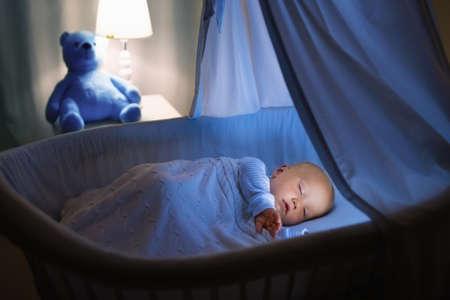 밤에 캐노피 푸른 요람에서 사랑스러운 아기 우유를 마시는. 침대, 램프와 장난감 곰 어두운 방에서 잠을 준비 공식 병 잠 옷에 어린 소년입니다. 아이