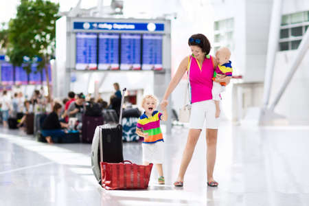 Family at airport before flight. Mother and kids waiting to board at departure gate of modern international terminal. Traveling and flying with children. Mom with baby and toddler boarding airplane.