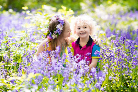 Kids with bluebell flowers, garden tools and wheelbarrow. Boy and girl gardening. Children play outdoor in bluebells, work, plant and water blue bell flower bed. Family fun in summer forest.