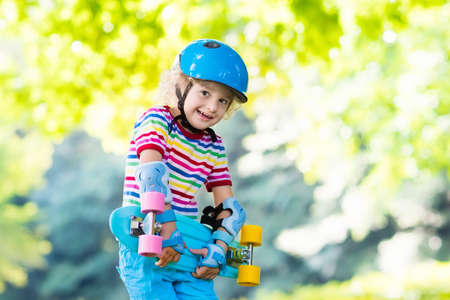 elbow pads: Child riding skateboard in summer park. Little boy learning to ride skate board. Active outdoor sport for school and kindergarten kids. Children skateboarding. Preschooler on longboard. Kid skating.