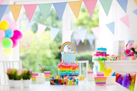 Decoración y pastel de la fiesta de cumpleaños de los niños. Decorado de mesa para la celebración de cumpleaños de niño. Rainbow pastel de unicornio para niña. Sala con globos festivos, pancartas de colores en color pastel bebé.