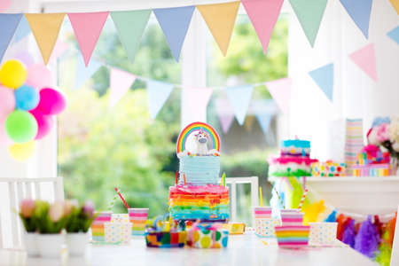 Kids birthday party decoration and cake. Decorated table for child birthday celebration. Rainbow unicorn cake for little girl. Room with festive balloons, colorful banners in baby pastel color. Stok Fotoğraf - 78956893