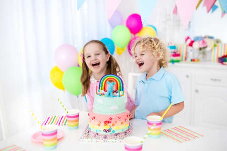 Kids birthday party with colorful pastel decoration and rainbow cake. Girl and boy with sweets, candy and fruit. Balloons and banner at festive decorated table for child or baby birthday party.