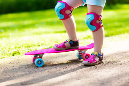 Child riding skateboard in summer park. Little girl learning to ride skate board. Active outdoor sport for school and kindergarten kids. Children skateboarding. Preschooler on longboard. Kid skating.