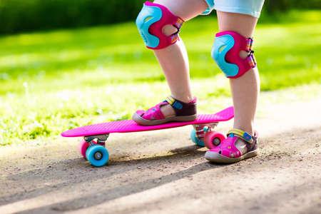 Kind rijden skateboard in zomer park. Meisje leert schaatsplank rijden. Actieve buitensport voor school en kleuterschoolse kinderen. Kinderen skateboarden. Kinderdagverblijf op longboard. Kidschaatsen.