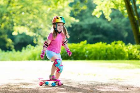 skate park: Child riding skateboard in summer park. Little girl learning to ride skate board. Active outdoor sport for school and kindergarten kids. Children skateboarding. Preschooler on longboard. Kid skating.