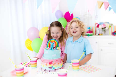 fruit candy: Kids birthday party with colorful pastel decoration and rainbow cake. Girl and boy with sweets, candy and fruit. Balloons and banner at festive decorated table for child or baby birthday party.