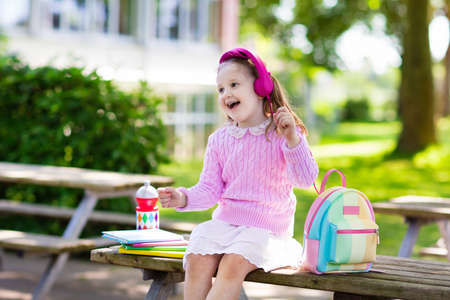 first day: Child going back to school. Start of new school year after summer vacation. Little girl with backpack and books on first school day. Beginning of class. Education for kindergarten and preschool kids.