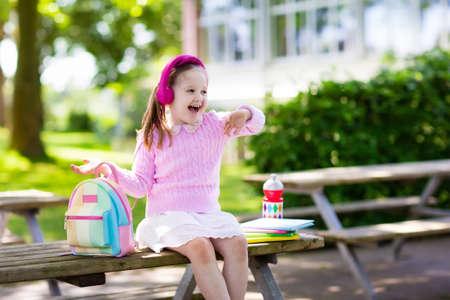 Kind gaat terug naar school. Begin van het nieuwe schooljaar na zomervakantie. Meisje met rugzak en boeken op de eerste schooldag. Begin van de les. Onderwijs voor kleuter- en kleuterscholen.