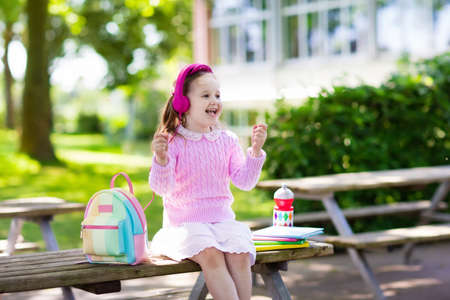 first year student: Child going back to school. Start of new school year after summer vacation. Little girl with backpack and books on first school day. Beginning of class. Education for kindergarten and preschool kids.