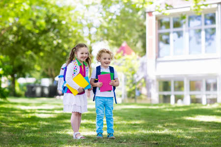 first day: Children go back to school. Start of new school year after summer vacation. Boy and girl with backpack and books on first school day. Beginning of class. Education for kindergarten and preschool kids. Stock Photo