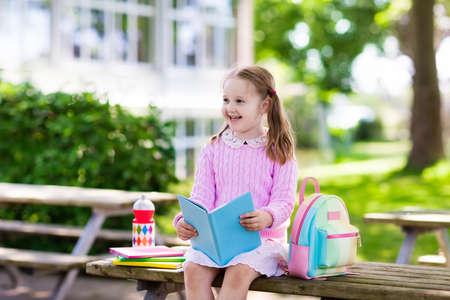 L'enfant retourne à l'école. Début de la nouvelle année scolaire après les vacances d'été. Petite fille avec sac à dos et livres en première journée scolaire. Début du cours. Éducation pour les enfants de maternelle et les enfants d'âge préscolaire. Banque d'images - 79082716