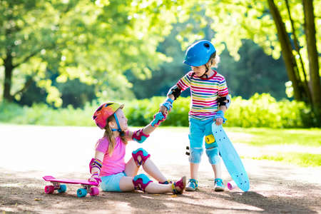 Children riding skateboard in summer park. Little girl and boy learn to ride skate board, help and support each other. Active outdoor sport for kids. Child skateboarding. Preschooler kid skating.