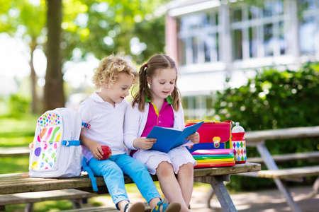 Kinderen gaan terug naar school. Begin van het nieuwe schooljaar na zomervakantie. Jongen en meisje met rugzak en boeken op de eerste schooldag. Begin van de les. Onderwijs voor kleuter- en kleuterscholen.