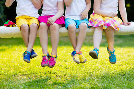 Footwear for children. Group of preschool kids wearing colorful leather shoes. Sandal summer shoe for young child and baby. Preschooler playing outdoor. Child clothing, foot wear and fashion. Stock Photo