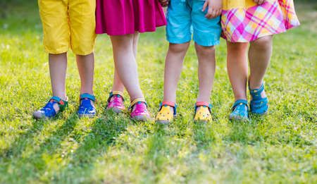 Footwear for children. Group of preschool kids wearing colorful leather shoes. Sandal summer shoe for young child and baby. Preschooler playing outdoor. Child clothing, foot wear and fashion. Stockfoto