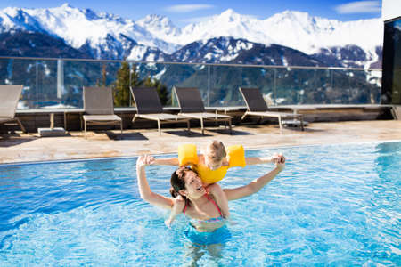 Mother and baby play in outdoor swimming pool of luxury spa alpine resort in Alps mountains, Austria. Winter and snow vacation for family with children. Kids in hot tub outdoors with mountain view.