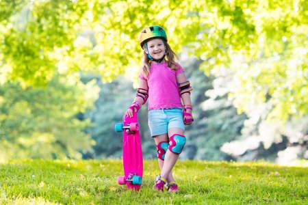 Child riding skateboard in summer park. Little girl learning to ride skate board. Active outdoor sport for school and kindergarten kids. Children skateboarding. Preschooler on longboard. Kid skating.