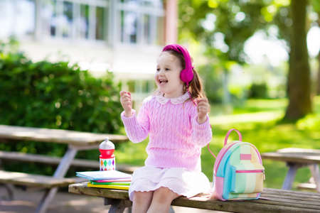 audio book: Child going back to school. Start of new school year after summer vacation. Little girl with backpack and books on first school day. Beginning of class. Education for kindergarten and preschool kids.