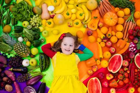 Bambina con varietà di frutta e verdura. Colorato arcobaleno di frutta fresca e verdura cruda. Bambino che mangia spuntino sano. nutrizione vegetariana per i bambini. Vitamine per i bambini. Vista dall'alto. Archivio Fotografico - 82123014