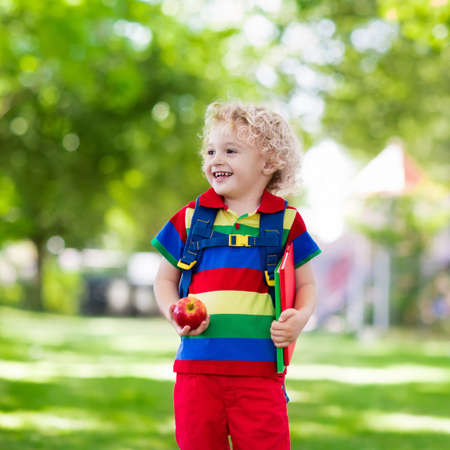 first year student: Child going back to school. Start of new school year after summer vacation. Little boy with backpack and books on first school day. Beginning of class. Education for kindergarten and preschool kids. Stock Photo