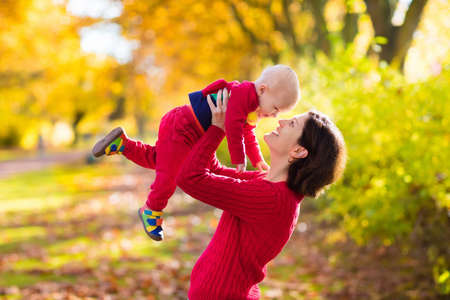 Mother and baby play in autumn park. Parent and child walk in the forest on a sunny fall day. Children playing outdoors with yellow maple leaf. Toddler boy play with golden leaves. Mom hugging kid. photo