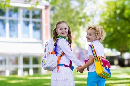 first year student: Children go back to school. Start of new school year after summer vacation. Boy and girl with backpack and books on first school day. Beginning of class. Education for kindergarten and preschool kids. Stock Photo