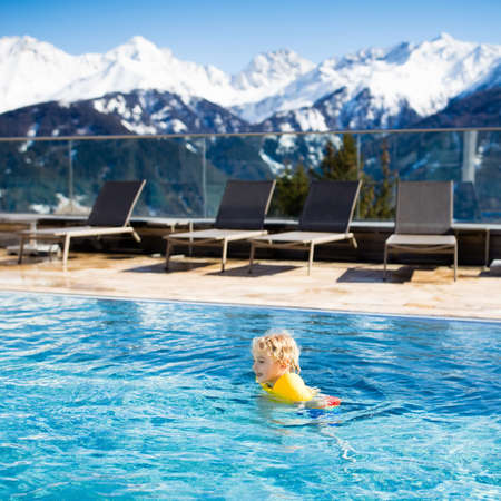 chairs: Little child playing in outdoor swimming pool of luxury alpine resort in the Alps mountains, Austria. Winter and snow vacation with kids. Hot tub outdoors with mountain view. Children play and swim.