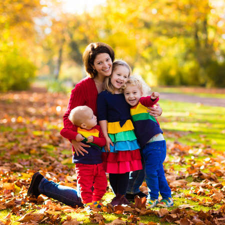 Mother and kids play in autumn park. Parent and children walk in the forest on a sunny fall day. Boy and girl playing outdoors with yellow maple leaf. Toddler picking golden leaves. Mom hugging kid. photo