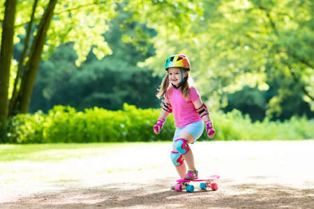 elbow pads: Child riding skateboard in summer park. Little girl learning to ride skate board. Active outdoor sport for school and kindergarten kids. Children skateboarding. Preschooler on longboard. Kid skating.