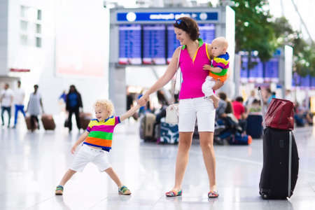 Family at airport before flight. Mother and kids waiting to board at departure gate of modern international terminal. Traveling and flying with children. Mom with baby and toddler boarding airplane. photo