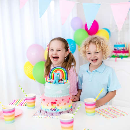 Kids birthday party with colorful pastel decoration and rainbow cake. Girl and boy with sweets, candy and fruit. Balloons and banner at festive decorated table for child or baby birthday party. photo