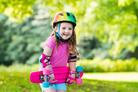 Child riding skateboard in summer park. Little girl learning to ride skate board. Active outdoor sport for school and kindergarten kids. Children skateboarding. Preschooler on longboard. Kid skating. photo