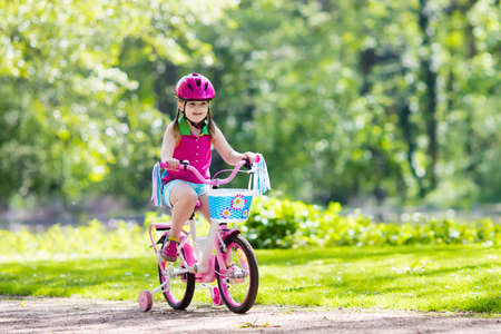 Child riding bike. Kid on bicycle in sunny park. Little girl enjoying bike ride on her way to school on warm summer day. Preschooler learning to balance on bicycle in safe helmet. Sport for kids. photo