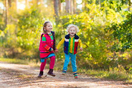 Kids playing in autumn park. Children play outdoors on a sunny fall day. Boy and girl running together hand in hand in a forest. Toddler and preschooler pick colorful oak leaf. Family fun outdoor photo