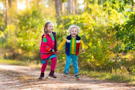 Kinderen spelen in de herfst park. De kinderen spelen buiten op een zonnige dag vallen. Jongen en meisje lopen samen hand in hand in een bos. Peuter en kleuter halen eikenblad kleurrijk. Family Fun outdoor