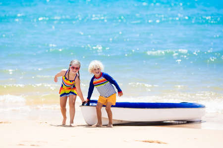 Kids kayaking in ocean. Children in kayak in tropical sea. Active vacation with young kid. Boy and girl in canoe on beautiful beach. Holiday activity with preschool child. Family summer fun.