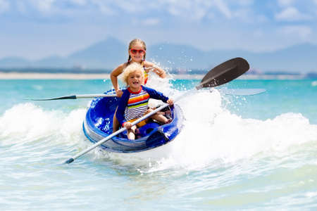 Kids kayaking in ocean. Children in kayak in tropical sea. Active vacation with young kid. Boy and girl in canoe on beautiful beach. Holiday activity with preschool child. Family water fun. Banco de Imagens